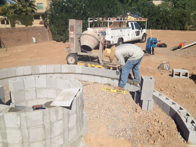 The masons are hard at work building exterior fire pit walls.