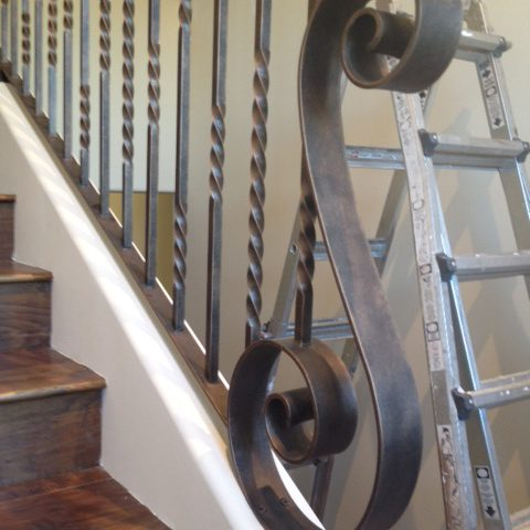 Beautiful ornamental railing leads up to the top floor complementing the natural wood staircase.