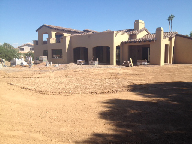 With the home almost complete, the rear-yard landscaping is one of the final stages. This view shows the lot before landscaping begins