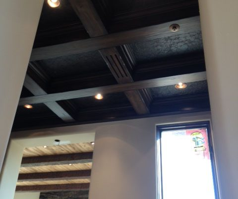 Wood beams adorn the ceiling contrasting the light wood in one room and complimenting the dark wood in another