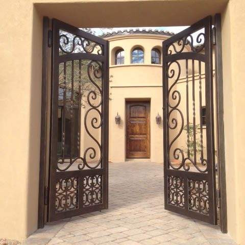 An elegant iron gate adorns the entry way welcoming guests and homeowners alike