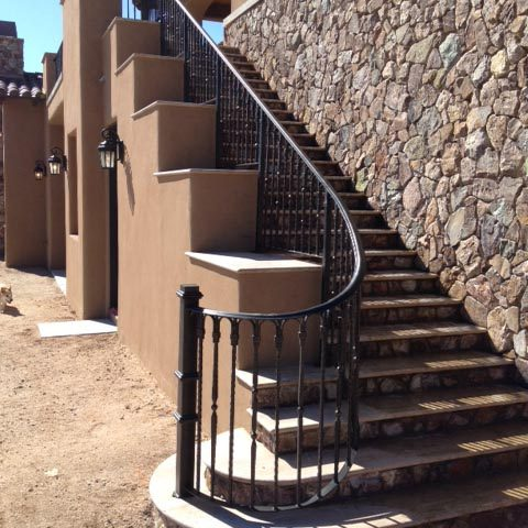 Iron, stone and stucco create multiple textures and depths to this exterior staircase.
