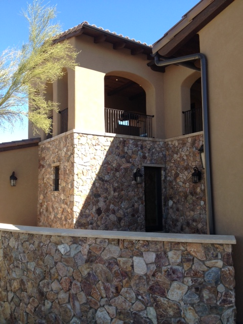 Splendid stonework accents the solid stucco trimmed by iron railings.