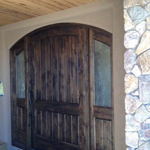 Gorgeous wood is contrasting with the light ceiling detail against the dark door creating a welcoming front entry.