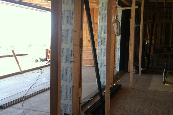Rough door openings along the top floor of the home leading out to a patio are ready for the doors to be installed.