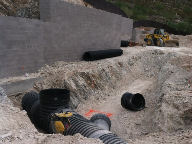 Large drain pipes are place in culverts to be covered by the earth and re-graded. Grading Equipment