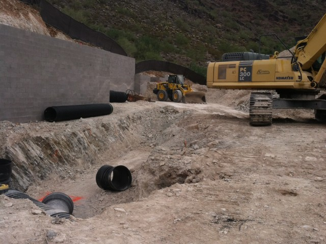 Grading equipment has finished the pad and dug culverts for the drain pipes. Set Drain Pipes