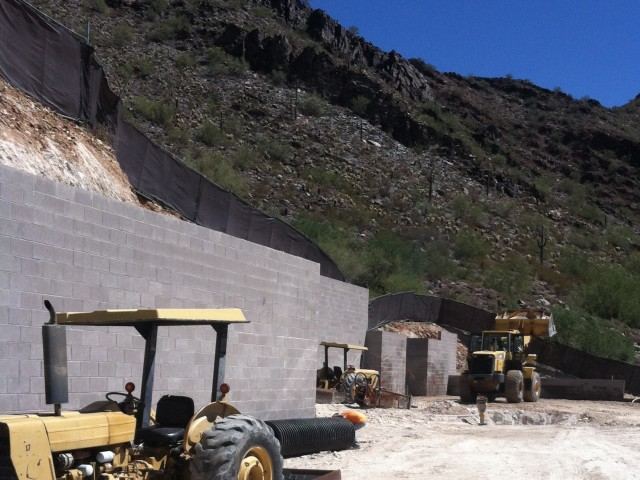 The construction fence ascends steeply above the site walls on this hillside project.