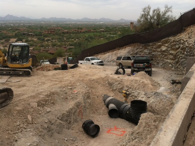 Expansive views can be seen from this home site. With the trucks, we can see by scale how large this pad is.