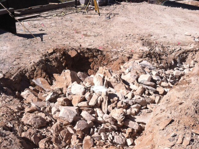 Rocks have been hammered out for the footings while a laser level gives proper elevation heights.