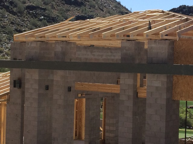 Trusses are atop framing and steel beam that runs across masonry columns.