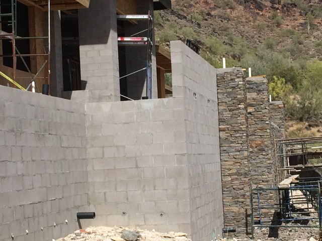 Stone is being applied to masonry walls to give a decorative view to the golfers on the adjacent course.