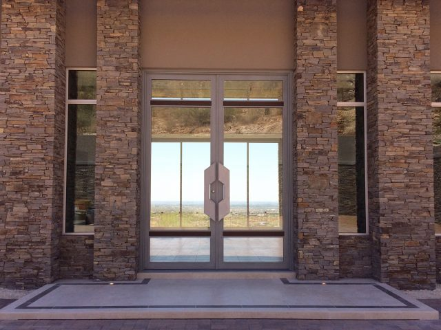 Stone columns frame in the picture-perfect views through the entry doors to the rear of the home.