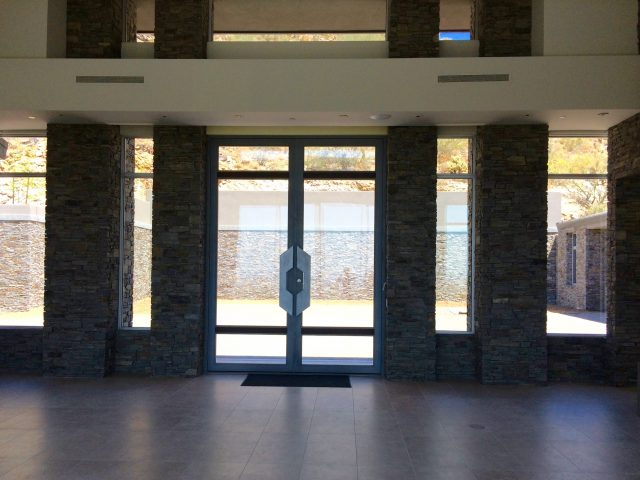The expansive courtyard and towering stone wall are seen from the Great Room's front view.