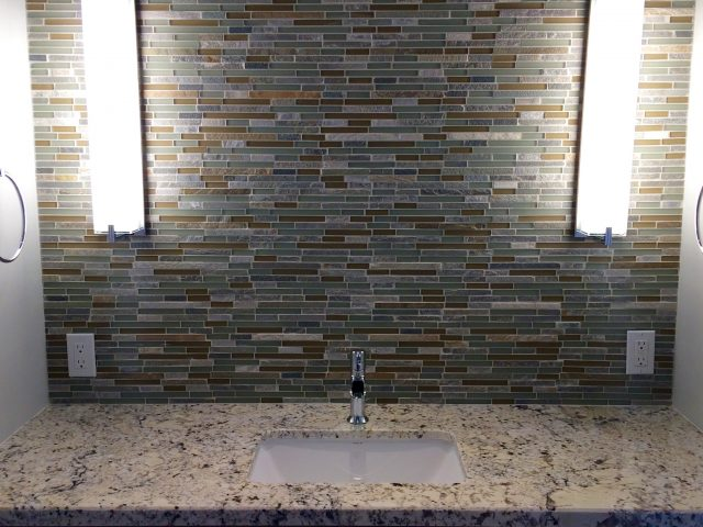 Custom tile wall with two vanity lights waiting for a mirror to complete the Guest House bathroom.