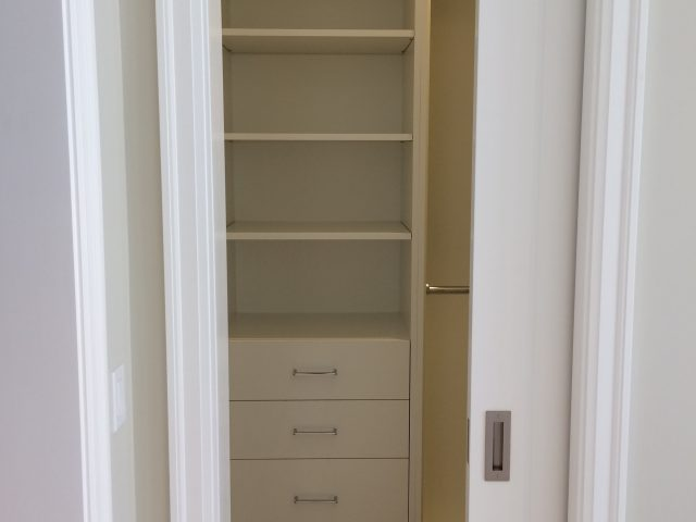 Spacious Guest House closet with custom shelving and a pocket door.