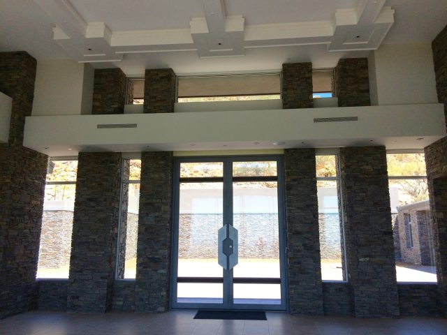 Magnificent entryway into the main home with floor-to-ceiling windows and towering stone columns.