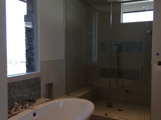 Separate tub and shower underneath windows for natural lighting.